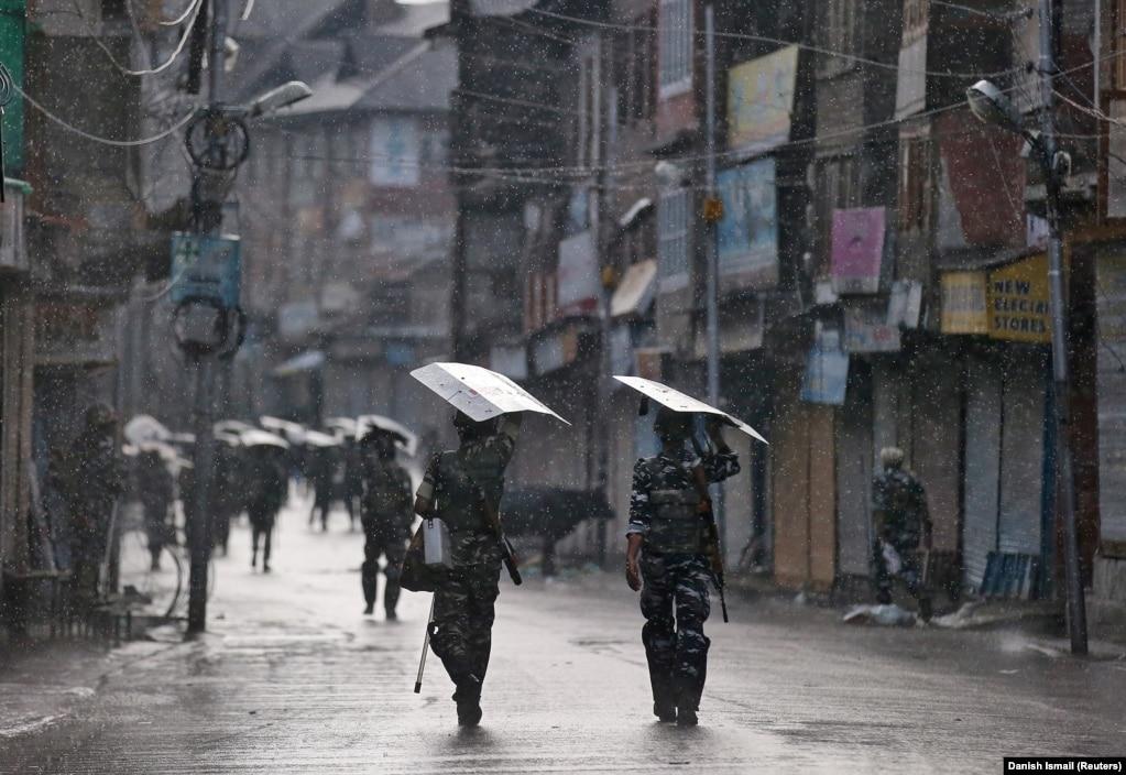 Индийская полиция патрулирует улицу в Сринагаре под дождем. После пересмотра правового статуса Кашмира Индия направила в регион десятки тысяч военнослужащих.