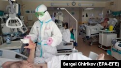 A medical-student volunteer takes care of a patient at an intensive-care unit at a Moscow hospital.