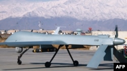 File photo of a drone armed with a missile setting off from its hangar at Bagram air base in Afghanistan.