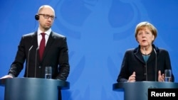 Ukrainian Prime Minister Arseniy Yatsenyuk and German Chancellor Angela Merkel address a news conference following talks at the Chancellery in Berlin on January 8.