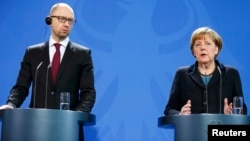 Ukrainanyň premýer-ministri Arseniý Ýatsenýuk (çepde) we Germaniýanyň kansleri Angela Merkel.