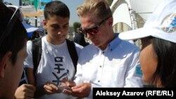 Олимпийский чемпион казахстанский велогонщик Александр Винокуров раздает автографы. Алматы, 4 октября 2015 года.