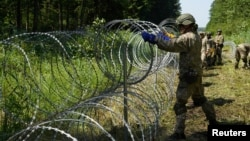 Lithuanian soldiers install razor wire on the border with Belarus on July 9.