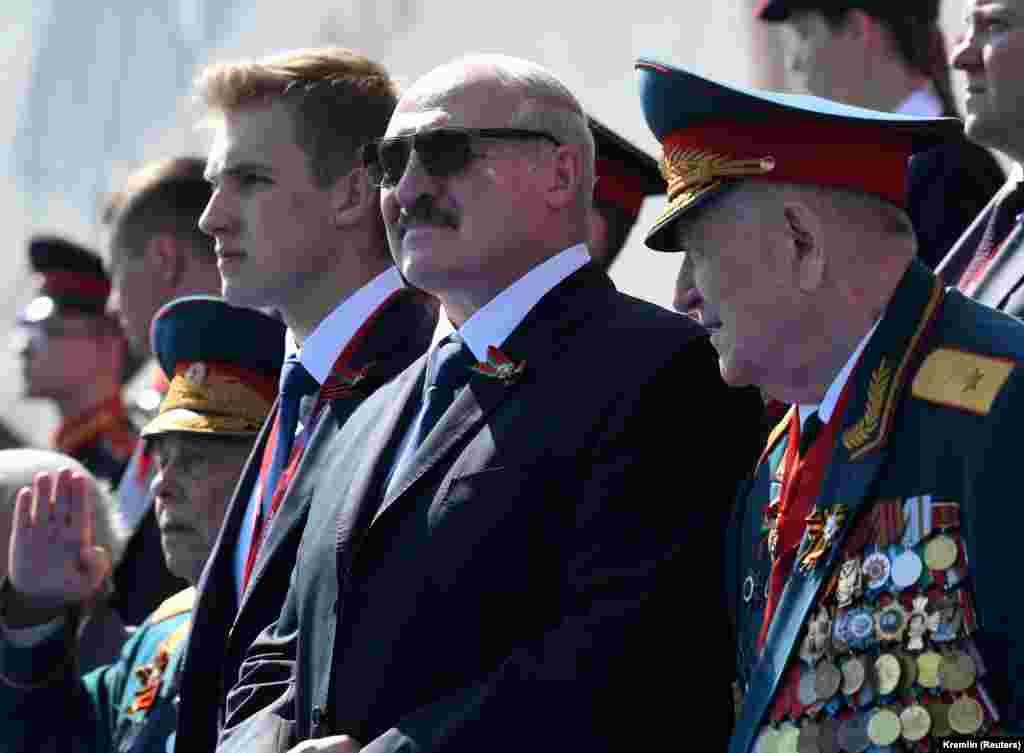 Президент Беларуси Александр Лукашенко наблюдает за парадом. В его стране, несмотря на пандемию, торжества по случаю 75-летия Победы, в том числе парад, прошли 9 мая. Власти Беларуси не объявляли карантин и не закрывали границы. В этой стране с населением около 9,4 миллиона человек, по официальным данным, на данный момент почти 60 тысяч зараженных и 362 смерти от COVID-19.