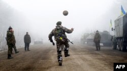 Ukrainian servicemen play soccer on a road at Svitlodarsk, approaching Debaltseve on February 15, hours after a cease-fire came into effect. The truce seems to have been cautiously observed by both sides, despite accusations by Kyiv and Washington that Russia had fueled a final push by rebels to gain territory before the start of the cease-fire.