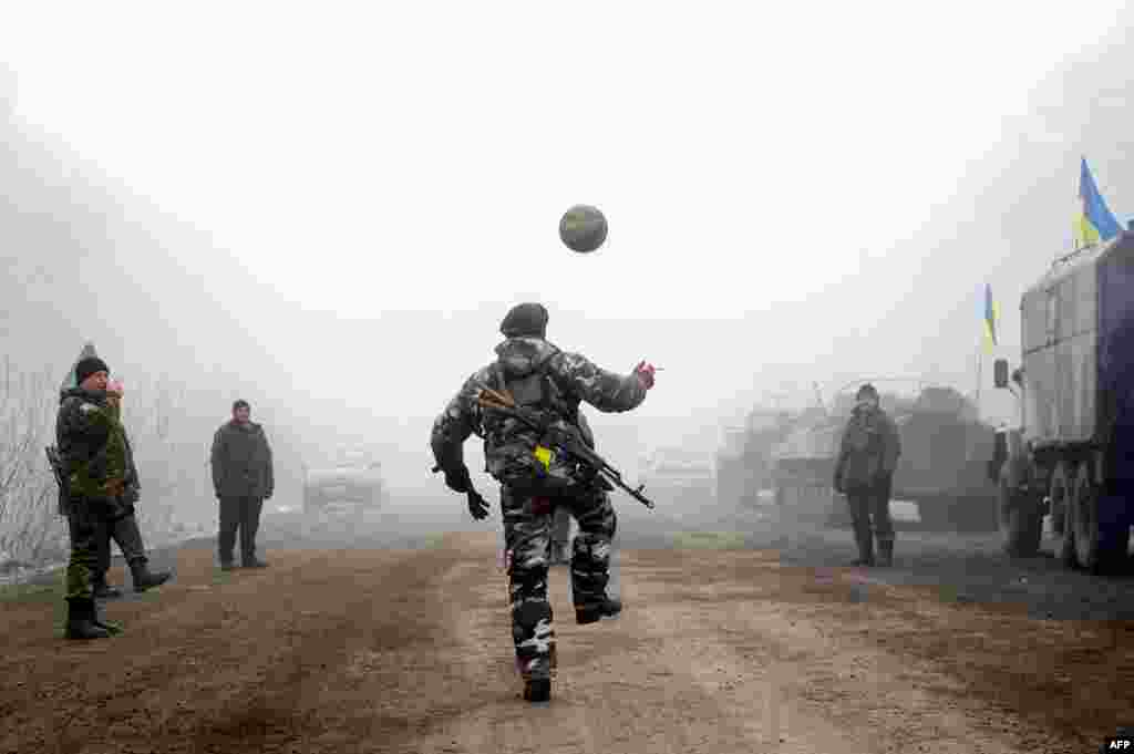 Ukrainian servicemen play football on a road near Debaltseve on February 15 shortly after a cease-fire began to be cautiously observed by both pro-Russian rebels and Kyiv forces in the country's months-long conflict. (AFP/Volodomyr Shuvayev)