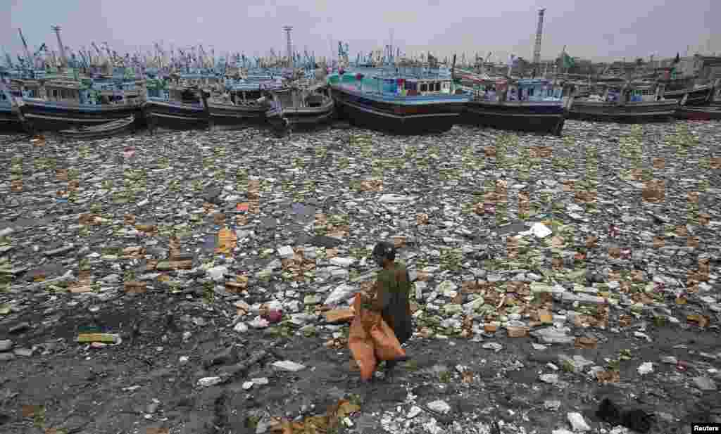A Pakistani boy looks to collect recyclable items among the polluted waters in front of fishing boats at Karachi Fish Harbor. (Reuters/Akhtar Soomro)