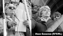 """Блага Димитрова, писател, дисидент и по-късно вицепрезидент, заедно с Анжел Вагенщайн, кинорежисьор и член на БКП, на стъпалата на храм-паметника """"Св. Александър Невски"""" пред петдесетхилядно множество на първия свободен митинг, 18 ноември1989 г. По-късно политическите убеждения ще разделят писателката и режисьора. Разделителната линия задълго ще остане в българското общество. Много знакови фигури на прехода ще преминават на """"другата страна""""."""