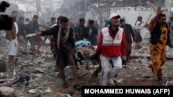 Yemeni medics and rescue workers carry a body on a stretcher at the site of reported airstrikes by Saudi-led coalition planes in the capital Sanaa on October 8.
