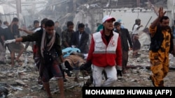 Медики и спасатели несут носилки с телами на месте авиаудара предположительно возглавляемой Саудовской Аравией коалиции. Сана, 8 октября 2016 года.