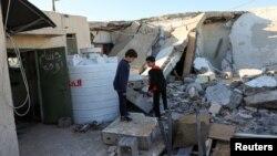 Соккудан ураган үйдүн жанында турган балдар. Ливия. 28-февраль, 2020-жыл.