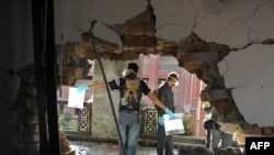 Investigators collect evidence at one of the two suicide blast sites at Islamic International University in Islamabad.