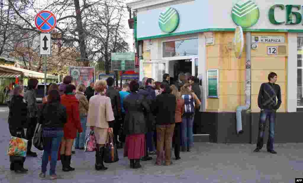 """Adamlar Aqmescitteki """"Sberbank Rossii"""" bankına kirmek içün öz nevbetini bekleyler, aprel 7 künü 2014 senesi"""