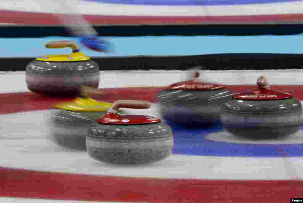 Red stones played by Canada and yellow ones played by Britain are seen in the house during their men's curling gold-medal game. Canada won. (Reuters/Laszlo Balogh)