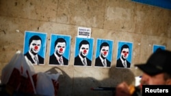 Ukraine -- A man eats next to defaced posters depicting President Viktor Yanukovych on Independence Square in Kyiv, December 4, 2013