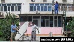 Работники снимают спутниковые антенны с домов в Ашгабате. 26 мая 2015 года.