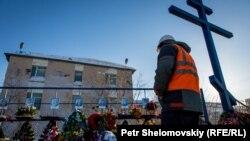 Северная кеніші кеңсесінің алдында шахтадағы апаттан қаза болған барлық кеншілердің фотосуреттері ілінген жерде тұрған адам.Воркута, Ресей, наурыз, 2016 жыл.