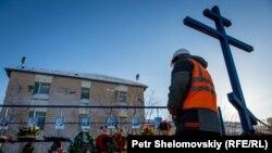 Шахтер у деревянного креста с фотографиями погибших при аварии коллег. Воркута, 6 марта 2016 года.