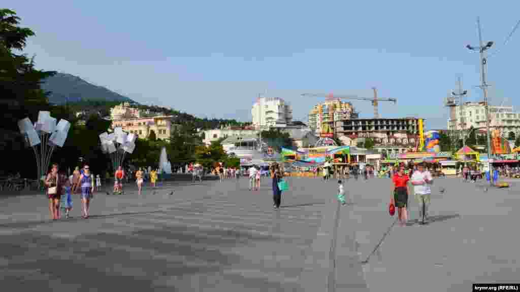 Набережною прогулюються люди. Позаду видніються встановлені на літній період атракціони.