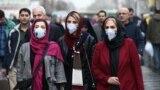 Iran -- Iranian women wearing protective masks to prevent contracting a coronavirus walk at Grand Bazaar in Tehran, February 20, 2020