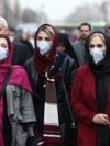 Iranian women wearing protective masks to prevent contracting coronavirus walk at Grand Bazaar in Tehran, February 20, 2020