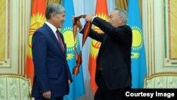 Qazaxıstan prezidenti Nursultan Nazarbaev Almazbek Atambaev-ə I dərəcəli «Dostık» ordeni verərkən. 7 noyabr, 2014-cü il