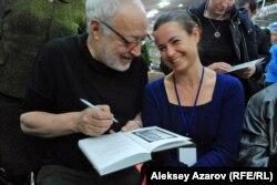 Ақын Бақыт Кенжеев оқырманға арнап кітабына қолтаңба жазып отыр.