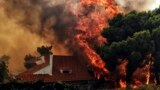 "Greece- A house is threatened by a huge blaze during a wildfire in Kineta, near Athens, on July 23, 2018. More than 300 firefighters, five aircraft and two helicopters have been mobilised to tackle the ""extremely difficult"" situation due to strong gusts o"