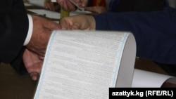 Кыргызстандын шайлоо тарыхында бул жолу эң узун (72 см.) бюллетен колдонулду.(Сүрөттө: Бишкектеги бир добушканада шайлоочуга бюллетен берилүүдө, 10-октябрь)