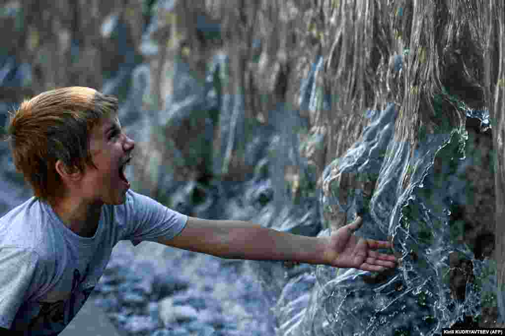 Хлопец шукае ахалоды ў фантане падчас сьпякотнага дня ў Максве.