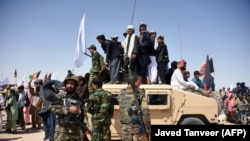 FILE: Afghan Taliban fighters and residents stand on a armored Humvee vehicle of the Afghan National Army (ANA) as they celebrate a ceasefire on the third day of Eid in Maiwand district of Kandahar Province in June 2018.