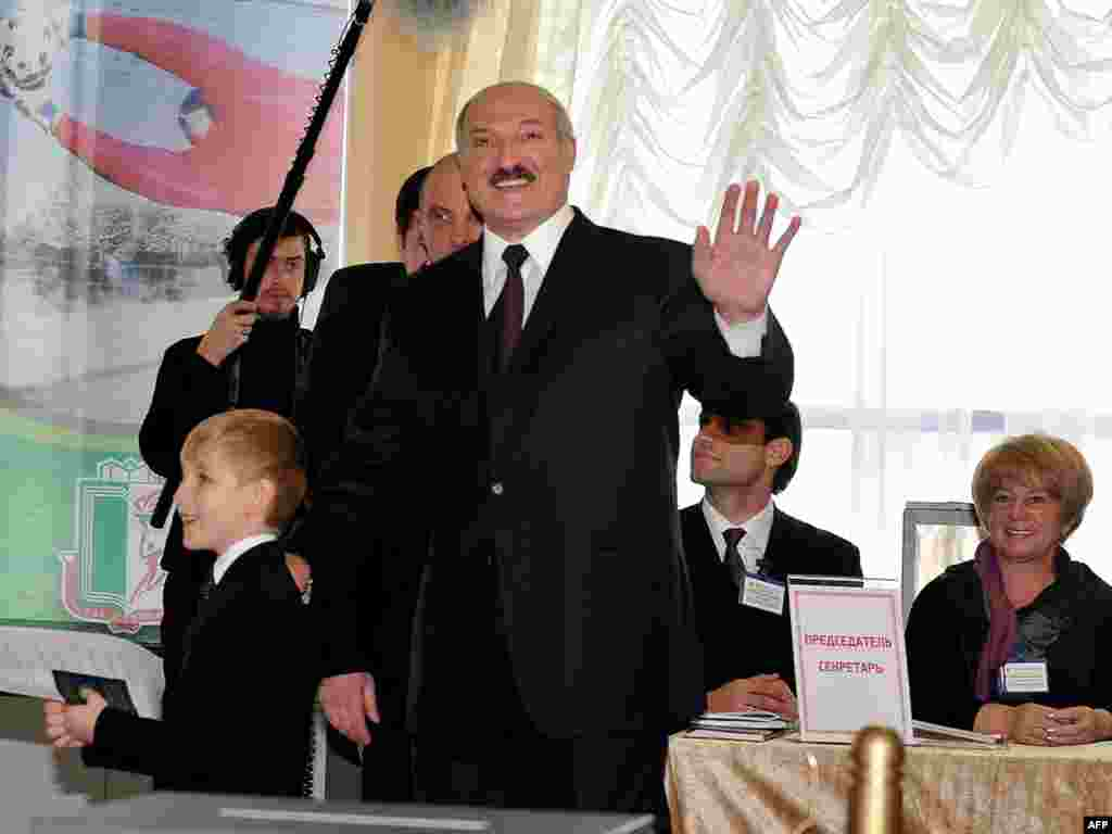 President Alyaksandr Lukashenka waves to journalists as he arrives with his young son to vote in Minsk.