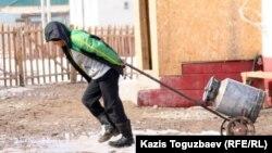 Қыс мезгілінде көшеде су әкеле жатқан бала. Алматы облысы. (Көрнекі сурет)
