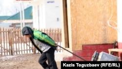 Он жастағы бала су тасып жүр. Алматы облысы, 9 наурыз 2011 жыл.