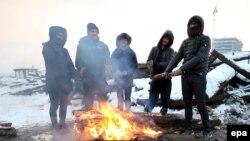 Мигранты греются у костра на территории заброшенного склада в Белграде, Сербия. 11 января 2017 года.