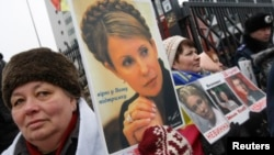 Supporters of jailed opposition leader and former Prime Minister Yulia Tymoshenko hold portraits of her during a rally in front of the appeals court building in Kyiv on February 15.