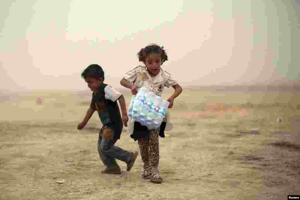 An Iraqi girl, who fled from the recent violence in Mosul, carries a case of water at a camp on the outskirts of Irbil, in the Kurdistan region on June 12. (Reuters)