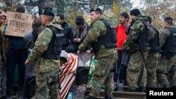 Pamje e migrantëve dhe forcave të sigurisë së Maqedonisë në kufirin me Greqinë afër qytetit Gjevgjeli