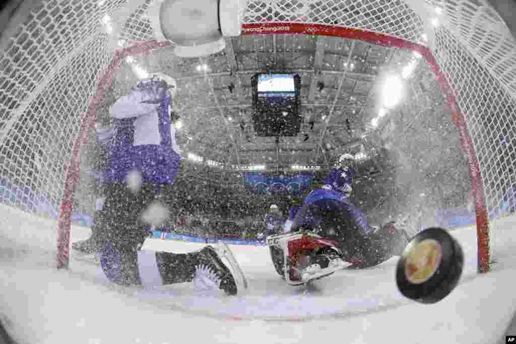 Хокей: Шайба, запущена Марією-Філіп Поулін з Канади, влітає у ворота під час другого періоду фіналу з жіночого хокею з командою США. Американські хокеїстки здобули перемогу з рахунком3:2.