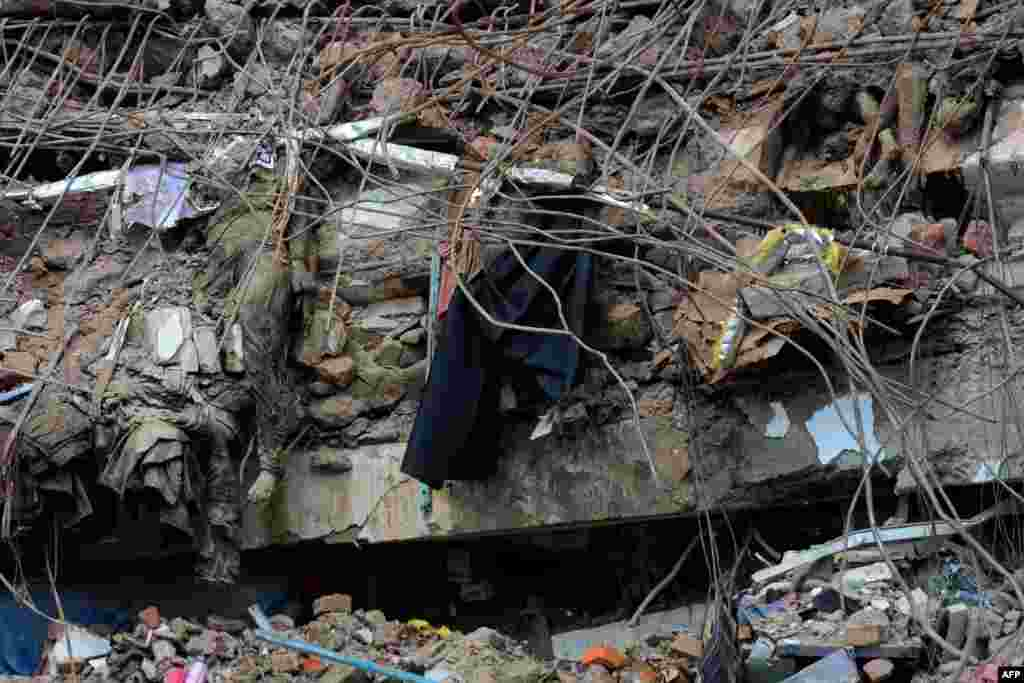 The bodies of Bangladeshi garment workers lie crushed under rubble after an eight-story building collapsed in Savar, on the outskirts of Dhaka. The death toll has passed 500. More than 100 people are still unaccounted for. (AFP/ Munir uz Zaman)