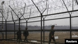 South Korean soldiers patrol along a barbed-wire fence, near the demilitarized zone that separates the two Koreas in Paju, north of Seoul.