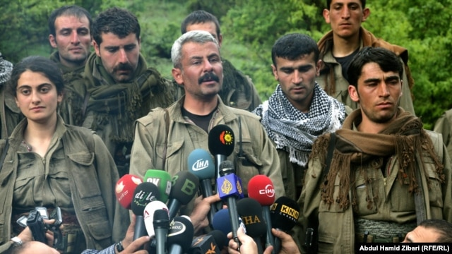 Jigar (one name), commander of the first group of withdrawing PKK fighters arriving in northern Iraq from Turkey, talks to reporters on May 14.