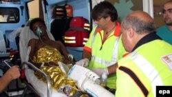 Италиялық құтқарушылар суға батқан кемеден тірі қалған адамды ауруханаға әкетіп барады. Италия, 3 қазан 2013 жыл.