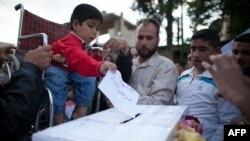 """طفل معاق يضع ورقة إقتراع مكتوب عليها """"شهيد"""" في الإنتخابات السورية"""