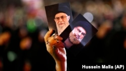 A Hizballah supporter holds up portraits of the group's leader, Sayyed Hassan Nasrallah (right), and Iranian Supreme Leader Ayatollah Ali Khamenei during a religious commemoration in the Lebanese capital, Beirut. (file photo)
