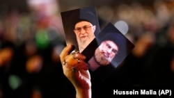 A Hizballah supporter in Beirut holds up portraits of the group's leader Sayyed Hassan Nasrallah and Iranian Supreme Leader Ayatollah Ali Khamenei (file photo)