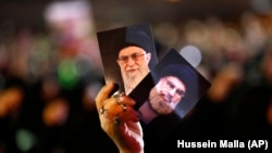 LEBANON -- A Hizballah supporter holds up portraits of Hizballah leader SayyedHassan Nasrallah and Iranian supreme leader Ayatollah Ali Khamenei during activities to mark the ninth of Ashura, a 10-day ritual commemorating the death of Imam Hussein, in Bei