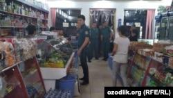 Сотрудники милиции требуют закрыть магазин «Диёра асал» в городе Газалкенте, 26 июля 2018 года.