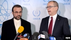 Iranian Ambassador to the IAEA Reza Najafi (left) and Tero Varjoranta, IAEA deputy director general and head of the Department of Safeguards, talk to journalists prior to a meeting in Vienna on December 11.
