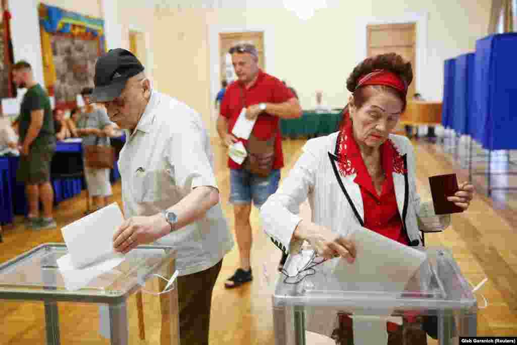 Виборці з Києва кидають бюлетені у виборчу скриньку